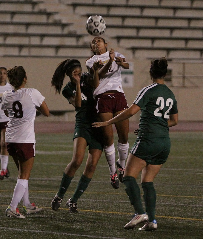 Kaylin Richards leaps over Vanessa Hernandez to head the ball during the 1-1 tie away at East Los Angeles College on Oct 4, 2013.  (Courier/Benjamin Simpson)