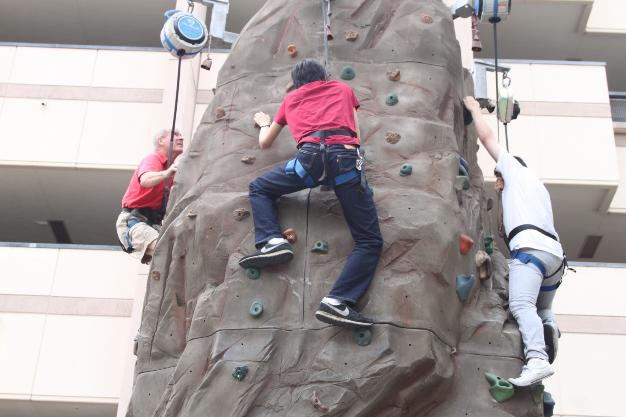 Nate Fermin/Courier Owner of Quantum Rock Fred Willis (left), Shawn Han 19 (mid), and Cam Duong 18 (right) attempt multiple levels of the rock wall featured in the middle of the PCC quad on September 3 2015. Quantum Rock and their rock wall tower over the quad for students to try for free.