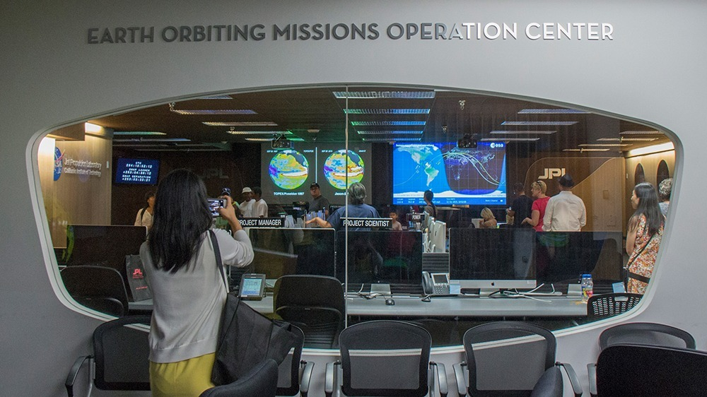 Keely Damara/Courier NASA employee Steven Collins explains to a group of children about the types of rovers and orbiters currently on Mars during the JPL open house on Sunday, October 11, 2015 in Pasadena, Calif. The open house was held on both Saturday and Sunday and included exhibits including a life-size model of the Curiosity Mars rover; demonstrations from numerous space missions; JPL's machine shop, where robotic spacecraft parts are built; and the Microdevices Lab, where engineers and scientists use tiny technology to revolutionize space exploration.