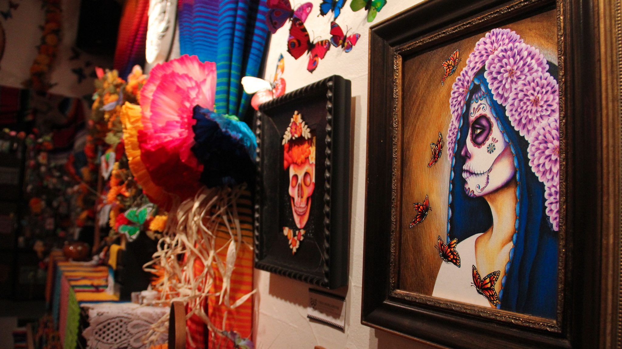 Elissa Saldana/Courier Attendees view calaca masks by one of the Artists at the 21st Annual Dia De Los Muertos event hosted by the Zona Rosa Caffe.