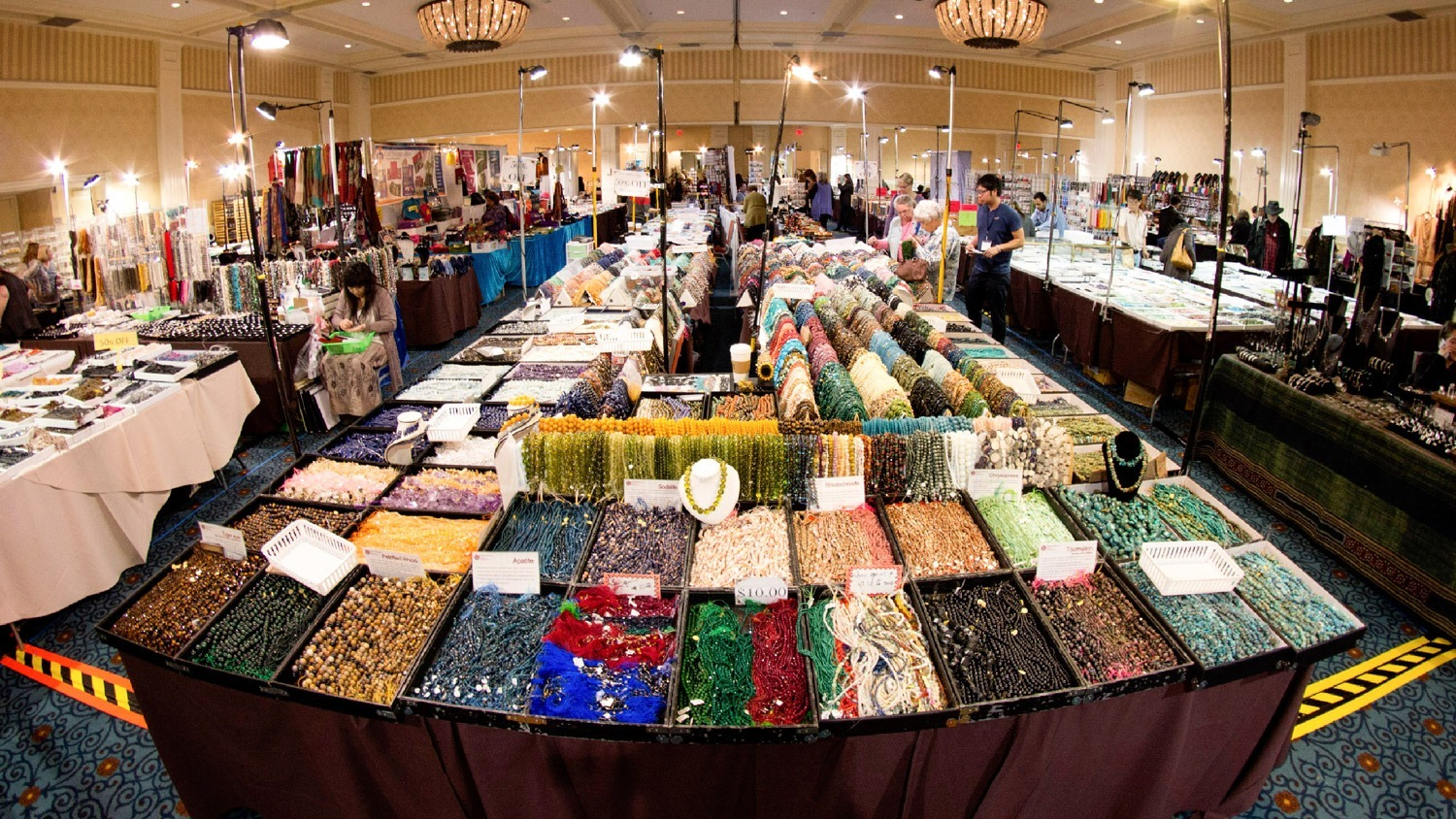 Katja Liebing/Courier Steffanie Ming, of Los Angeles, a former Pasadena City College student, looks at beads and other merchandise she considers buying at the Pasadena Bead & Design Show in the Hilton Hotel in Pasadena on Friday, January 15, 2016. It is one of five shows produced by Garan-Beadagio LLC and offers a selection of artisan booths, galleries, workshops and merchant displays.